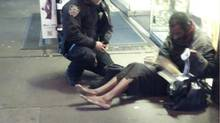 New York police officer Larry DePrimo gives a homeless man a pair of boots and socks in Times Square in this November 14, 2012 handout photo courtesy of Jennifer Foster. The photograph has drawn a deluge of praise after it was published on the police department's Facebook page this week. (Jennifer Foster/Reuters)