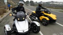 In this file photo provided by Can-Am Spyder, test riders pull out onto the highway for a test ride at the unveiling of the 2008 Can-Am Spyder roadster in Del Mar, Calif. U.S. safety regulators are investigating two reports of fires in Can-Am Spyder three-wheeled motorcycles. (Denis Poroy/THE ASSOCIATED PRESS)