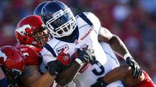 Toronto Argonauts' Cory Boyd, right, gets held up by Calgary Stampeders' Corey Mace, left, during first quarter CFL football action in Calgary, Alta., Friday, July 1, 2011. (The Canadian Press)