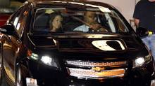 U.S. President Barack Obama sits next to plant manager Teri Quigley as he drives a Volt car off the assembly line at a General Motors auto plant in Hamtramck, Mich. (LARRY DOWNING/LARRY DOWNING/REUTERS)