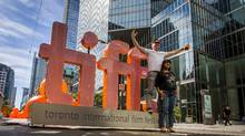 People pose on a giant TIFF sign on King St during the 40th Toronto International Film Festival in Toronto, Canada, September 10, 2015. TIFF runs from September 10-20. (MARK BLINCH/REUTERS)