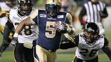Winnipeg Blue Bombers' Chad Simpson (5) dodges the tackle from Hamilton Tiger-Cats' Jamall Johnson (28) and Matt Bucknor (26) during the second half of their CFL game in Winnipeg Friday, September 21, 2012. (John Woods/THE CANADIAN PRESS)