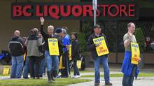 Striking B.C. Government and Service Employees' Union workers wave at passing vehicles at the liquor distribution branch on East Broadway in Vancouver on July 3, 2012. (Jeff Vinnick for The Globe and Mail)