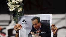 A woman holds up flowers and an image of late prosecutor Alberto Nisman while waiting for the hearse with his remains, in Buenos Aires January 29, 2015. Argentine prosecutor Nisman who died under mysterious circumstances the day before he was to testify in Congress about allegations against the president regarding an investigation into a 1994 bombing, was buried on Thursday amid calls for justice. (MARCOS BRINDICCI/REUTERS)