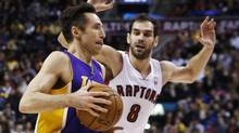 Los Angeles Lakers' Steve Nash drives to the net against Toronto Raptors' Jose Calderon, right, during the first half of their NBA basketball game in Toronto on Sunday. (MARK BLINCH/REUTERS)