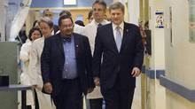 Stephen Harper, right, chats with Arthur Porter, left, at the Montreal General hospital in 2006. The Prime Minister had Dr. Porter sworn in as a member of the Privy Council. (Ryan Remiorz/The Canadian Press)