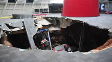 In this image provided by the National Corvette Museum shows several cars that collapsed into a sinkhole Wednesday, Feb. 12, 2014, in Bowling Green, Ky. (National Corvette Museum/Handout/Associated Press)
