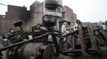 A man walks past damaged machine parts in front of a house that was burned by an angry mob on Sunday night, in Gujranwala, July 28, 2014. A Pakistani mob killed a woman, who lived in the house and was member of a religious sect, and two of her granddaughters after a sect member was accused of posting blasphemous material on Facebook, police said Monday, the latest instance of growing violence against minorities. (MOHSIN RAZA/REUTERS)