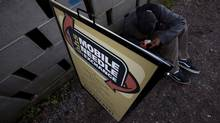 An addict uses the sign for the Portland Hotel Society's mobile needle exchange program to block the wind as he tries to smoke a rock of crack in an alley in Abbotsford, B.C., on July 5, 2012. (Jonathan Hayward/The Canadian Press)