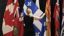A staff worker fixes flags before the first news conference of Canadian premiers at the 55th Annual Premiers' Conference in Charlottetown August 27, 2014. REUTERS/Christinne Muschi (CANADA - Tags: POLITICS) (CHRISTINNE MUSCHI/REUTERS)