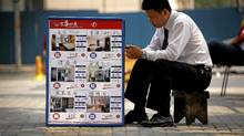 A real estate agent sits next to a board displaying prices for residential apartments in central Beijing. Home prices are falling in the Asian nation. (David Gray/Reuters/David Gray/Reuters)