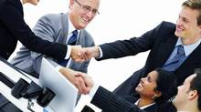 A group of business people shake hands (Jacob Wackerhausen/iStockphoto)