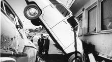 An automobile became pinned under house after tsunami waves struck Port Alberni, following an earthquake in Alaska in 1964. (IAIN MCKAIN/The Canadian Press)