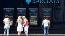 People use a line of Barclays cash dispensers in central London, June 28, 2012. (PAUL HACKETT/Reuters)