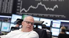 A trader works at his desk in front of the DAX board at the Frankfurt stock exchange July 11, 2012 (ALEX DOMANSKI/REUTERS)