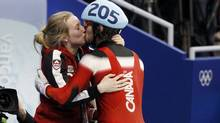 Canada's Charles Hamelin (R) kisses his girlfriend Marianne St-Gelais as he celebrates his gold medal after the men's 500 metres short track speed skating final at the Vancouver 2010 Winter Olympics, February 26, 2010. (JERRY LAMPEN)
