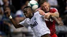 Vancouver Whitecaps' Gershon Koffie, left, of Ghana, and Toronto FC's Danny Califf vie for the ball during the second half of an MLS game in Vancouver, B.C., on Saturday March 2, 2013. (DARRYL DYCK/THE CANADIAN PRESS)