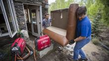 Gordon MacPherson, left, a home owner in Discovery Ridge,with the help of a friend removes a water soaked couch from his flooded basement June 22, 2013. (John Lehmann/The Globe and Mail)
