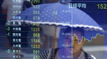 A woman holding an umbrella is reflected in an electronic stock quotation board outside a brokerage in Tokyo July 14, 2014. Asian shares rose on Monday as euro zone banking jitters faded. (ISSEI KATO/REUTERS)