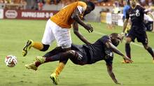 Toronto FC's Jermain Defoe (18) falls to the ground as he is hit by Houston Dynamo's Warren Creavalle, left, during the second half of a MLS soccer game Saturday, July 19, 2014, in Houston. (Associated Press)
