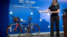 Craig Premack, who was shot while riding on the Trans-Canada Highway at 1 a.m. during an overnight road cycling event near Spences Bridge, B.C., in June, shows where the bullet entered his forearm during a news conference at RCMP headquarters in Surrey, B.C., on July 29, 2014. (Darryl Dyck/The Canadian Press)