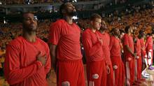 Members of the Los Angeles Clippers listen to the national anthem before Game 4 of an opening-round NBA basketball playoff series against the Golden State Warriors on Sunday, April 27, 2014, in Oakland, Calif. The Clippers chose not to speak publicly about owner Donald Sterling. Instead, they made a silent protest. The players wore their red Clippers' shirts inside out to hide the team's logo. (Marcio Jose Sanchez/AP)