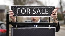 An agent puts up a 'for sale' sign in Toronto. (Darren Calabrese For The Globe and Mail)
