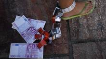 A demonstrator hangs fake Euro notes on her leg during a protest against Spain's bailout at La Constitucion square in Malaga, southern Spain, June 10, 2012. (JON NAZCA/REUTERS)