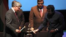 "Prime Minister Stephen Harper, Parliamentary Secretary to the Minister of Foreign Affairs Deepak Obhrai and High Commissioner of India to Canada, Shashishekhar M. Gavai light an oil lamp at the launch of the ""Year of India in Canada 2011"" at the Museum of Civilization in Gatineau on Friday, March 4, 2011. (PATRICK DOYLE/PATRICK DOYLE/THE CANADIAN PRESS)"