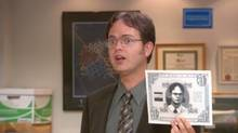 "Dwight Schrute, played by actor Rainn Wilson, holds a ""Schrute Buck,"" a a reward system he devised for employees who please him during a brief but tyrannical reign as branch manager"
