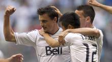 Vancouver Whitecaps' Alain Rochat celebrates with teammates Young-Pyo Lee and Sebastien Le Toux (JONATHAN HAYWARD/The Canadian Press)