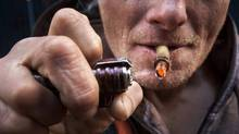 A crack cocaine addict uses a crack pipe to get high in Vancouver's Downtown Eastside January 30, 2009. (John Lehmann/The Globe and Mail/John Lehmann/The Globe and Mail)