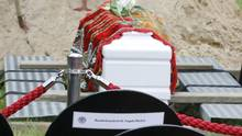 A coffin containing the remains of a female refugee stands in front of an empty seat for German Chancellor Angela Merkel during a muslim funeral at Gatow cemetery in Berlin, Germany, June 16, 2015. The body of a female refugee from Syria who had drowned in international waters in March 2015 at Europe's external borders, was brought to Berlin to be laid to rest by the project group 'The Center for Political Beauty', as a protest against the European Union's asylum policies, mass drownings in the Mediterranean and inhuman burial practices, a spokesman of the project group said. (Fabrizio Bensch/Reuters)