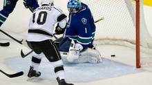 Los Angeles Kings' Mike Richards, left, scores the tying goal against Vancouver Canucks' goalie Roberto Luongo during third period NHL hockey action in Vancouver, B.C., on Monday November 25, 2013. (DARRYL DYCK/THE CANADIAN PRESS)