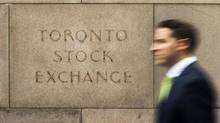 A man walks past an old Toronto Stock Exchange sign in Toronto on June 23, 2014. (Mark Blinch/Reuters)