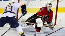 Nashville Predators' Colin Wilson, left, looks on as Calgary Flames goalie Miikka Kiprusoff, from Finland, swats away the puck during third period NHL hockey action in Calgary, Alta., Tuesday, Nov. 29, 2011. The Calgary Flames beat the Nashville Predators 1-0.THE CANADIAN PRESS/Jeff McIntosh (Jeff McIntosh/CP)
