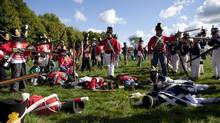 Scouts dressed as Canadian and British soldiers, left, fire back and forth with American soldiers, right, during a re-enactment of the War of 1812 by Scouts Canada and Boy Scouts of America at Fort George in Niagara-on-the-Lake, Ont., on Sept. 23, 2012. (Matthew Sherwood For The Globe and Mail)