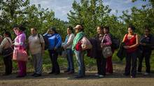 A group of temporary foreign workers wait to board a bus for the short ride to work before a 13 hour shift at the Jealous Fruit sorting and packing plant in Kelowna August 22, 2014. (John Lehmann/The Globe and Mail)
