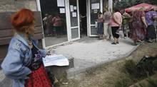 Local residents stand in line to get benefit payments outside the rebel headquarters in Donetsk, eastern Ukraine, Tuesday, Aug. 19, 2014. (Max Vetrov/AP)