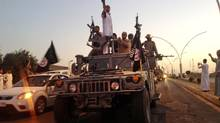 In this file photo taken June 23, 2014, militants from the Islamic State parade in a commandeered Iraqi security forces armoured vehicle on a main street in Mosul, Iraq. (Uncredited/AP)