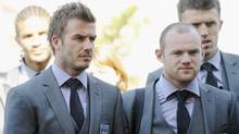 The England soccer team, including (L-R) David Beckham and Wayne Rooney, arrives at the Royal Bafokeng Sports Campus, in Rustenburg, South Africa June 3, 2010. A cluster of local workers, police and security guards and a pack of television crews welcomed the England World Cup squad to their Rustenburg base in warm sunshine on Thursday. REUTERS/Michael Regan/Pool (POOL)