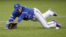 Troy Tulowitzki of the Toronto Blue Jays dives for a ball hit by Kansas City Royal Alcides Escobar in the fourth inning of game five of the American League Championship Series Oct 21, 2015 in Toronto. (Mark Blinch For The Globe and Mail)