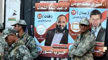 Egyptian soldiers stand in front of campaign posters for candidates from the hard-line Islamist Salafist al-Nour party in the coastal city of Alexandria on Monday. (AFP/Getty Images/AFP/Getty Images)