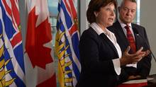 B.C. Premier Christy Clark and Education Minister Peter Fassbender talk about the ongoing teachers' dispute at a news conference in Vancouver on Sept.3, 2014. (Jonathan Hayward/The Canadian Press)