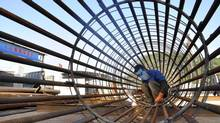 A worker welds steel bars at a construction site for a new train station in Ningbo, Zhejiang province, China, Dec. 6, 2012. (CHINA DAILY/REUTERS)