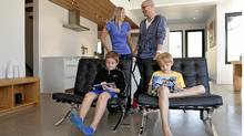 Melissa and Geoff Teehan and their children Sam (left front) and Cole, in their new accessible home in the Beaches neighbourhood of Toronto. They built the home after Melissa suffered a sudden illness and became paralyzed. (Della Rollins/Della Rollins for the Globe and)