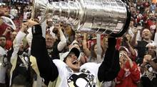 Pittsburgh Penguins captain Sidney Crosby raises the Stanley Cup after his team beat the Detroit Red Wings to win Game 7 of the tournament finals last June in Detroit. (Paul Sancya)