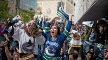 Vancouver Canucks fans react at CBC plaza to the first goal in the first period by the Canucks during game 5 of the NHL Western Conference Final against the San Jose Sharks in Vancouver, British Columbia, Tuesday, May 24, 2011. (Rafal Gerszak For The Globe and Mail)