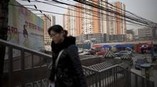A woman walks on a pedestrian overpass near a real estate project in Beijing on Monday, Feb. 27, 2012. China needs a new economic strategy after three decades of rapid growth and must reduce the dominance of state companies and promote free markets to achieve its goal of becoming a high-income society, the World Bank and Chinese researchers said Monday. (Alexander F. Yuan/Alexander F. Yuan/Associated Press)