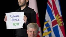A protester rushes the stage as Prime Minister Stephen Harper speaks at the Vancouver Board of Trade on Monday, Jan. 6, 2014. Vancouver police say they won't be pursuing criminal charges against two climate-change protesters who came within touching distance of the PM. (JONATHAN HAYWARD/THE CANADIAN PRESS)